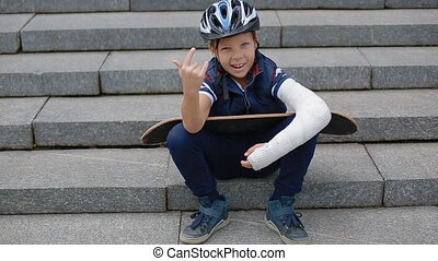 White boy with broken arm makng the rock sign