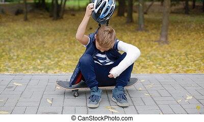 White boy with broken arm put of his helmet