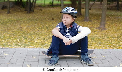 White boy with broken arm sitting on his skate