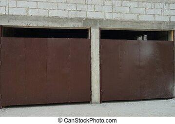 white brick garage facade with two brown iron gates