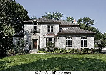 White brick home with cedar shake roof