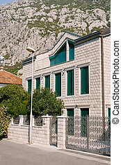 White brick house with green shutters and a fence with metal bars at the foot of the mountain.