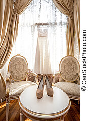 white bridal shoes and dress at luxurious bedroom -...