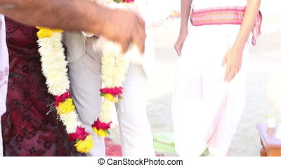 white bride and groom throwing rice into fire