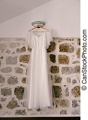 White bride dress on a wooden hanger against a stone wall with a sconce in a room with a sloping ceiling.