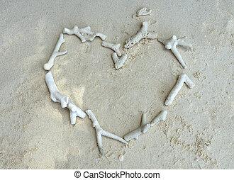 White broken dead coral in heart shape on the beach.
