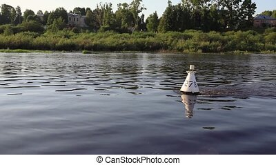 White buoy on the river waves on the background of the...