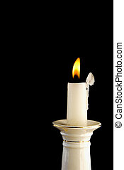 White burning candle in candlestick
