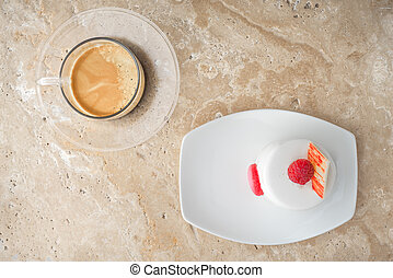 White cake with raspberry and coffee on the stone table