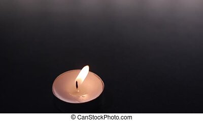 white candle burning with yellow shades and blow off with light smoke after extinguished. in slow motion on black Background. illustration of remembrance or celebration. High quality FullHD footage