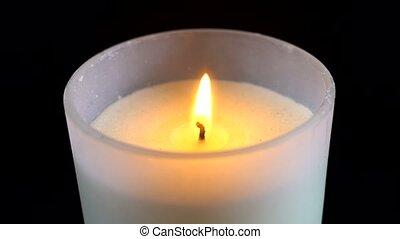 White candle close-up on black background