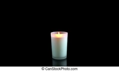 White candle lit on a black background