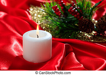 White candle on red satin background