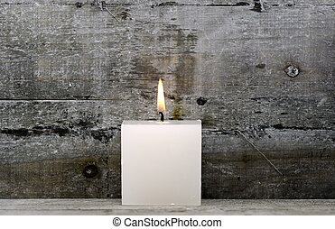 white candle - a white candle on wood background