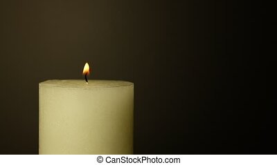 White candle trembling flame over black - Close up one white...