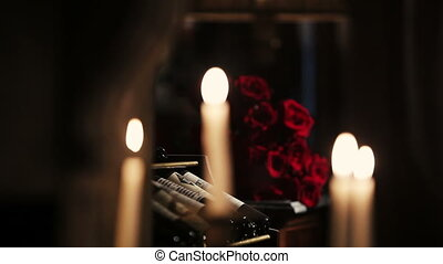 White candles burning. Fire. Bouquet of red roses on background. Flame