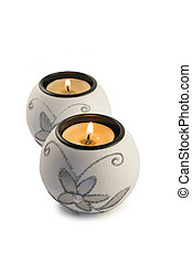 White candlestick with ball-shaped lighting candle on a white background