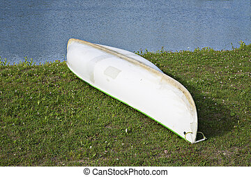 White canoe lay on green grass