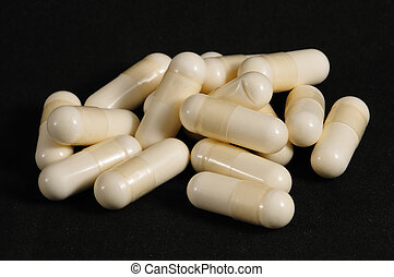 White capsules on a black background