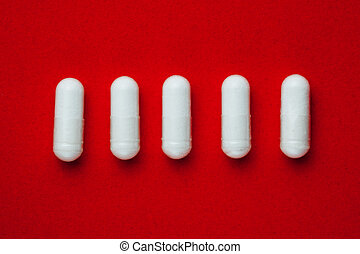 white capsules pills on red background