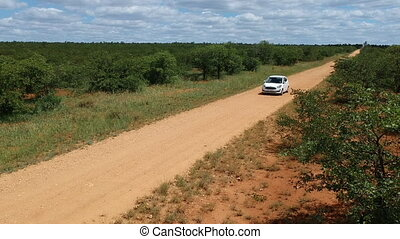 White car on sandy savannah road in Africa. High angle view.