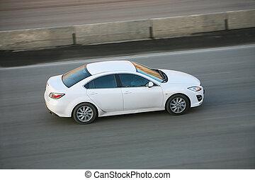 white car driving on city street