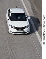 white car driving on street