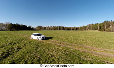 white car goes on the field