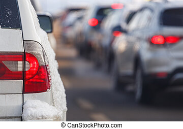 white car tail light with snow and blurry traffic in the background at winter day