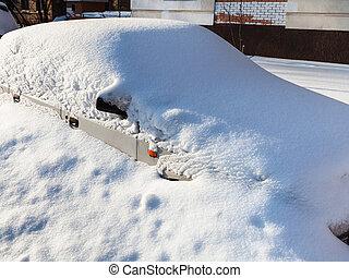 white car under snowdrift in parking lot