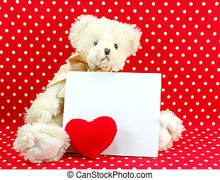 white card and cute teddy bear doll with red heart on red polka dot background