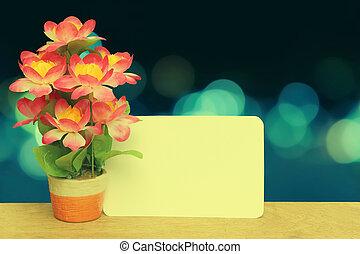 white card and flower vase on blur bokeh light in city in blue tone