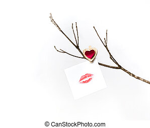 White card with lip print hanging on a bare winter tree branch pinned with a clothespin with a red heart for Valentine's Day