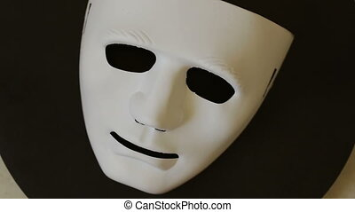 White carnival mask on a black background, in motion. -...