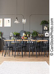 White carpet in grey dining room interior with black chairs at wooden table under lamps. Real photo