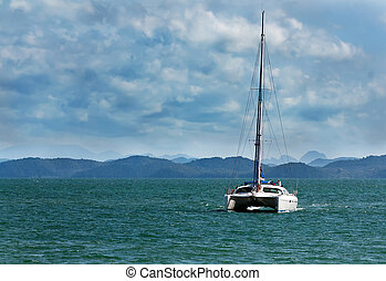 white catamaran with a flat sail against the backdrop of ...