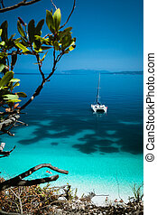 White catamaran yacht at anchor on clear azure surface with dark pattern in calm blue lagoon. Unrecognizable tourists relax on airbed in water near the beach