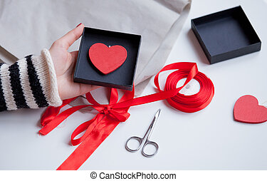 white caucasian hand holding heart shaped toy in box on the wonderful things for decoration background