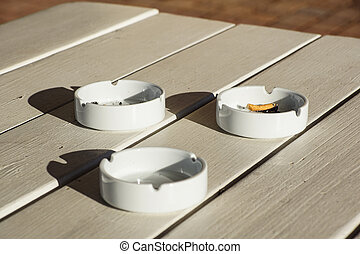 White ceramic ashtray on a wooden background