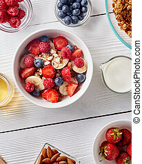 White ceramic bowl with natural organic berries, fruits, nuts, milk, muesli on wthite wooden background.