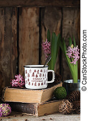 White ceramic cup of coffee on old books on rustic wooden background with cones and hyacinth