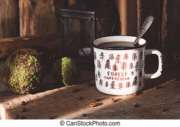 White ceramic cup of coffee on old books on rustic wooden background with cones