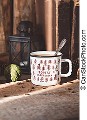 White ceramic cup of coffee on rustic wooden background with cones old books and a lantern