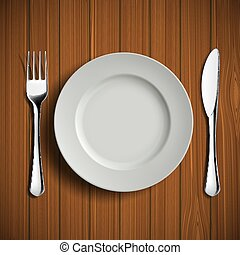 White ceramic plate, fork and knife on a wooden table. Table lay