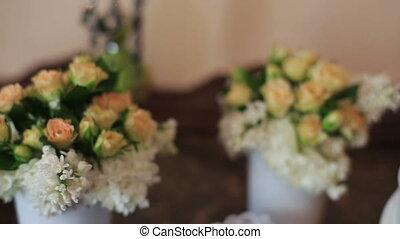 White ceramic sitting angels kissing on flowers background.