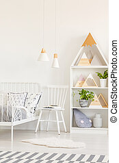 White chair and fur next to kid's bed in bright bedroom interior with plants and triangles. Real photo