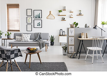 White chair at desk in spacious apartment interior with gallery above grey sofa near window. Real photo