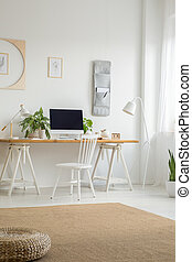 White chair at desk with computer desktop in home office interior with pouf on carpet. Real photo