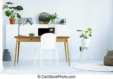 White chair at wooden desk with laptop and lamp in white home office interior. Real photo