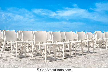 White chair group on blue sky.